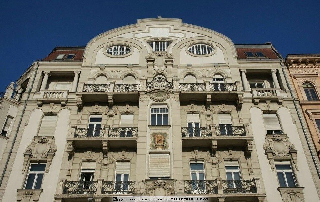 楼裙装饰 雕塑的窗户 花式拦杆的阳台 棕灰色砖外墙 日光 蓝天 建筑